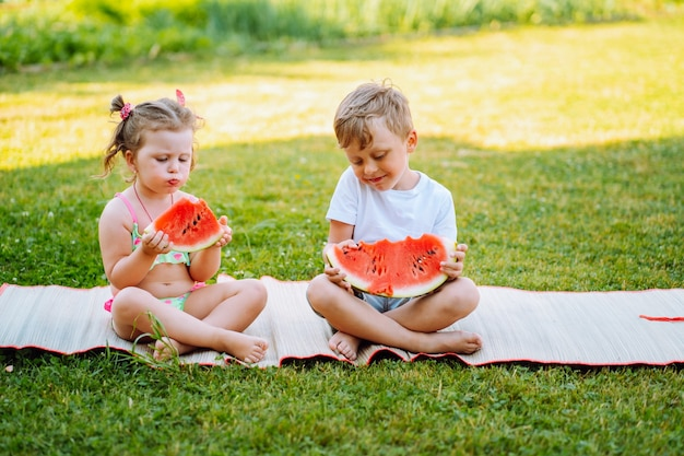 Two kids eat watermelon in the garden. kids eat fruit outdoors. healthy snack for children.toddlers girl and boy enjoy watermelon