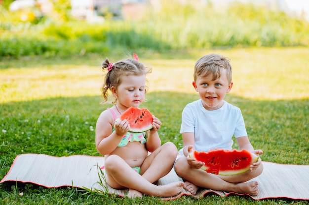 Two kids eat watermelon in the garden. kids eat fruit outdoors. healthy snack for children.toddlers girl and boy enjoy watermelon.
