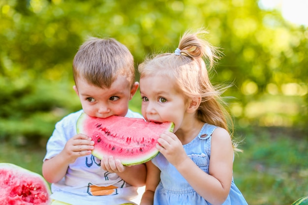 Two kids eating one slice of watermelon in the garden. kids eat fruit outdoors. healthy snack for children.