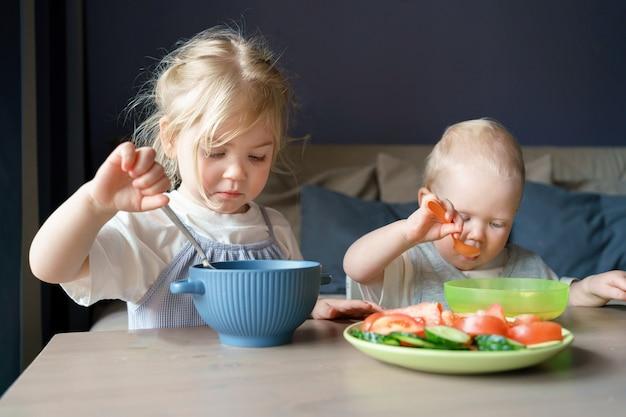 Двое детей едят суп и овощи на обед дома