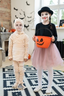Two kids in halloween attire standing in domestic room