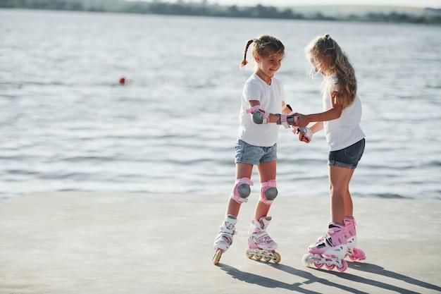 湖の近くで昼間にローラースケートに乗る方法を学ぶ2人の子供