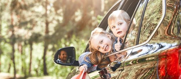 父親が車の家族の遠征を運転している間、窓の外を見ている2人の子供