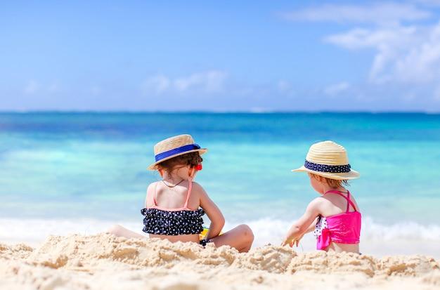 砂の城を作り、熱帯のビーチで楽しんでいる2人の子供