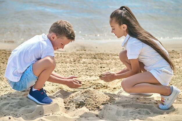 Двое детей строят замки из песка и выглядят вовлеченными
