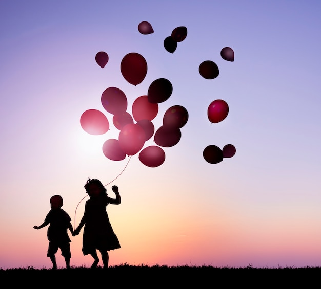 Two kids outdoor holding balloons together