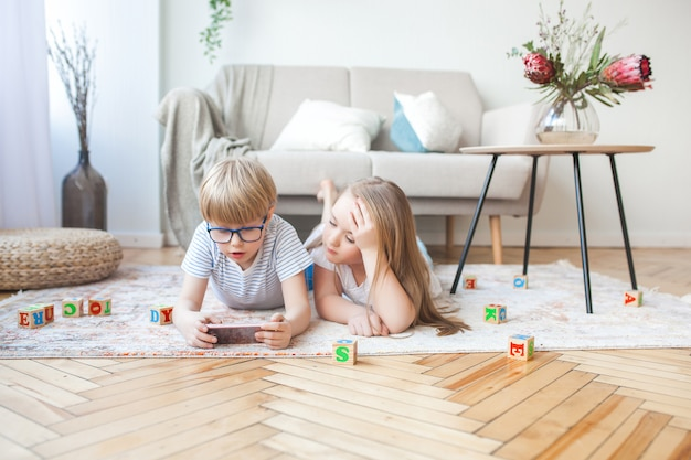 Two kids playing smartphone. boy and girl at home watching at the cell phone. digital children indoor.