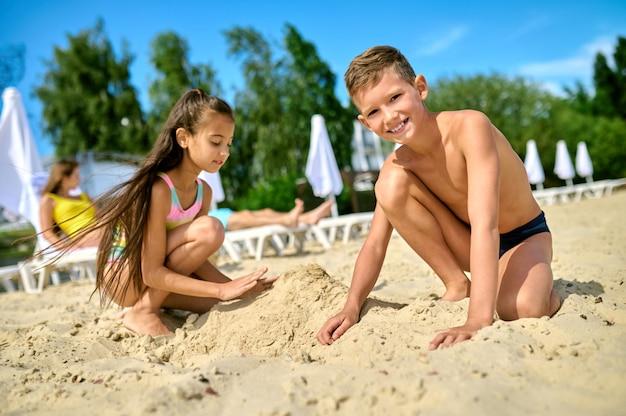 Двое детей играют с песком на пляже