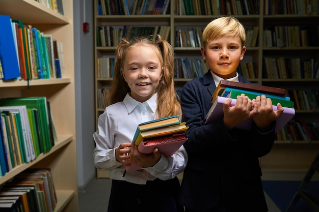 Two kids prepared for school, they stand holding stack of books in hands, looking at camera, wearing schools outfit