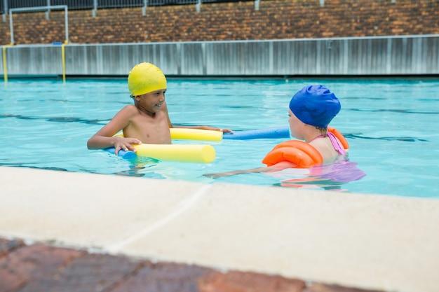 Двое детей плавают в бассейне в развлекательном центре
