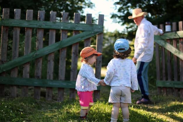 2人の子供が祖父を歩く
