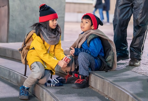 Two kids wearing winter clothing is sitting on a stair