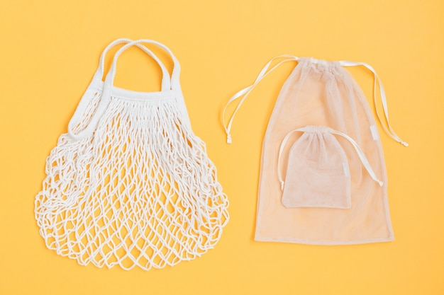 Two kind of reusable shopping bags on color background.