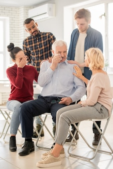 Two kind women and guys supporting aged man in grief during psychological session