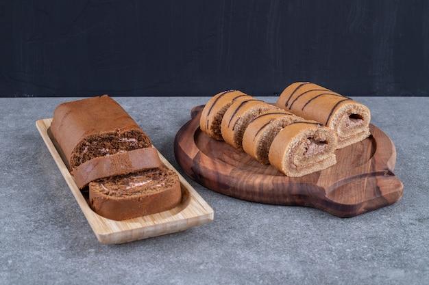 Due tipi di rotolo di torta al cioccolato su piatti di legno