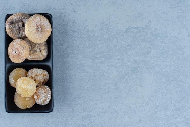 Due tipi di frutta secca nella ciotola, sul tavolo di marmo.