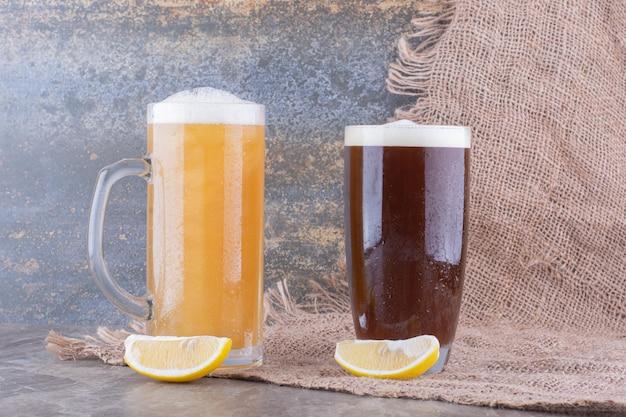 Два вида пива на мраморном столе с лимонами. фото высокого качества