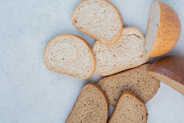 Два вида ломтиков хлеба на мраморном фоне. фото высокого качества