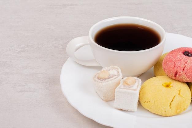 白いお皿に2種類のクッキー、お菓子とお茶。