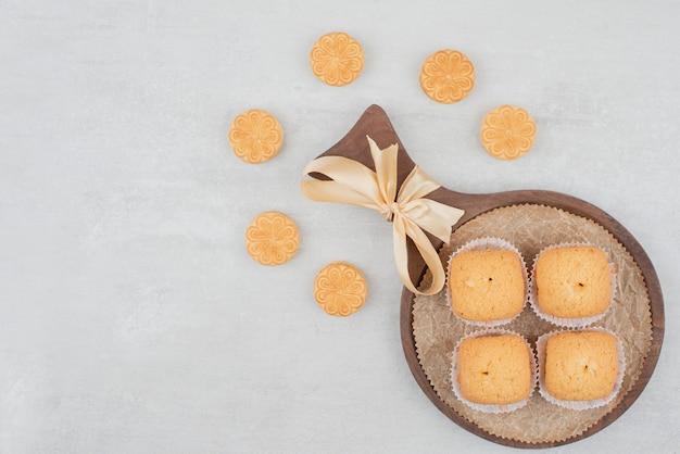 나무 접시에 크림과 함께 두 종류의 쿠키.