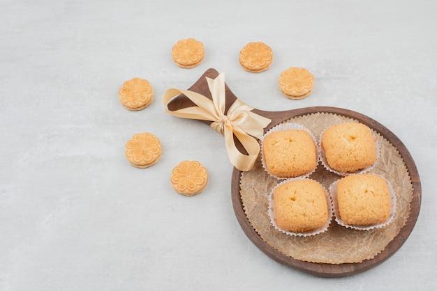 Два вида печенья со сливками на деревянной тарелке