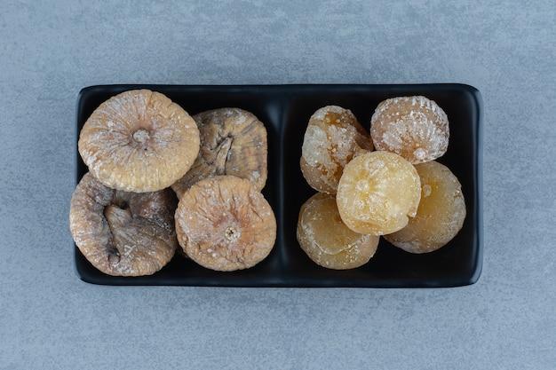 ボウルの中の大理石のテーブルの上にある2種類のドライフルーツ。