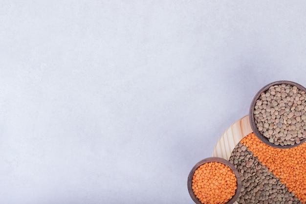 木の板とボウルに2種類の生豆とレンズ豆。