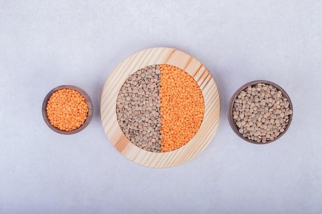 木の皿とボウルに2種類の生豆とレンズ豆。