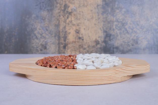 Два вида сырых бобов и гороха в деревянной тарелке.
