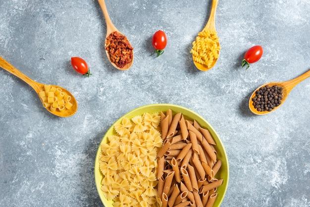 Два вида сырых макарон на тарелке с различными специями.