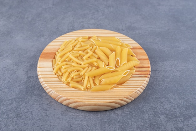Two kinds of pasta on wooden plate.