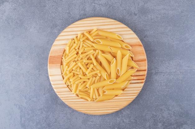 Due tipi di pasta sul piatto di legno.