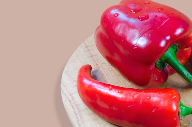 Two kinds of peppers on a wooden board