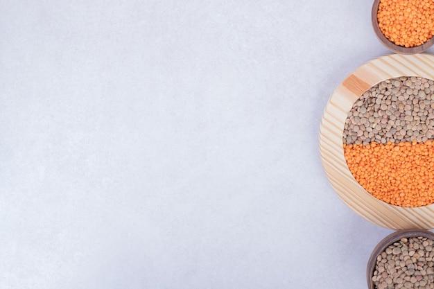 Due tipi di fagioli e lenticchie crudi in piatto e ciotole di legno.