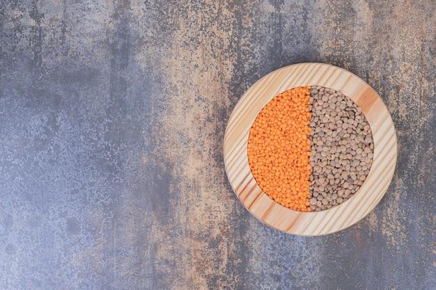 Due tipi di fagioli e lenticchie crude nel piatto di legno.