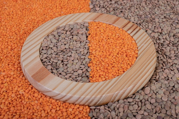 Two kinds of raw beans and lentils in wooden plate.