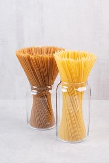 Two kinds of spaghetti inside glass jars.