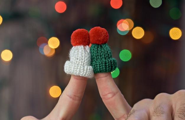 カラフルなクリスマスライトの背景にニット帽子の2つのキスの指