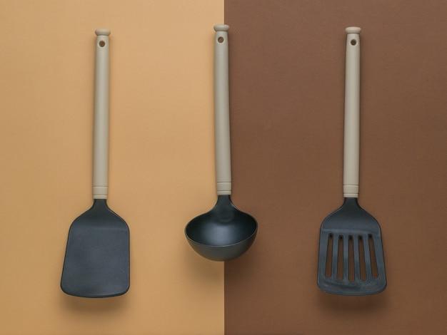 Две кухонные лопатки и черпак на двухцветном фоне. плоская планировка.