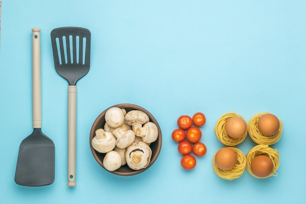 Two kitchen spatulas, pasta, eggs, mushrooms and tomatoes on a blue background. ingredients for making pasta.