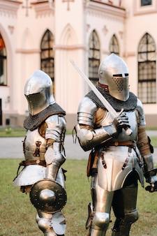 Два рыцаря в доспехах на фоне средневекового коссовского замка. средневековая концепция. металлическая текстура.
