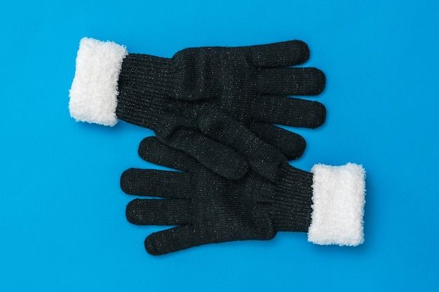 Two knitted gloves hug each other on a blue background. the concept of hope and meeting. fashion women's accessories.