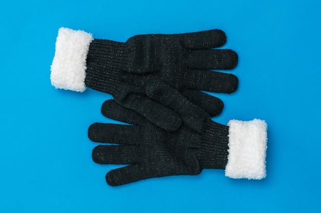2つのニット手袋は青い背景でお互いを抱きしめます。希望と出会いのコンセプト。ファッションレディースアクセサリー。