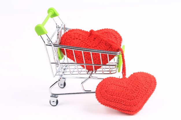 Two knitted hearts in a shopping cart on a white background. creative valentines day concept