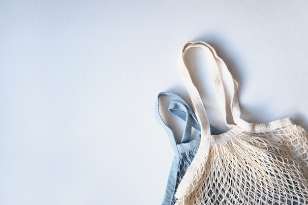 Two knitted mesh eco shopping bags on a light surface