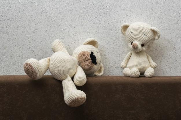 明るい壁に向かってソファの上に編まれた2匹のホッキョクグマ。美しいニットのおもちゃ。