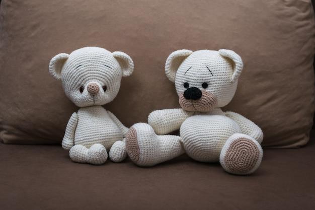 柔らかい茶色のソファに2匹のホッキョクグマのニット。美しいニットのおもちゃ。