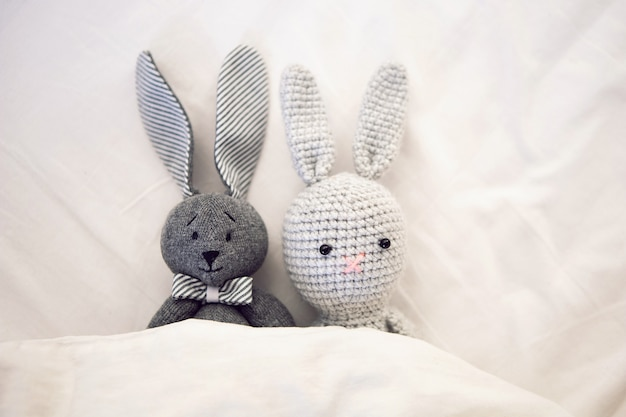Two knitted rabbit toys lie under a blanket in a white bed