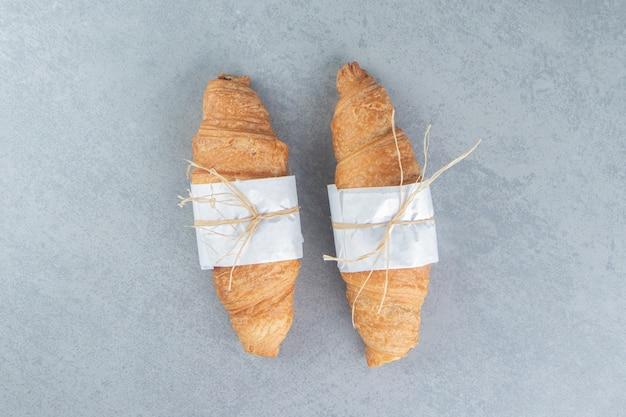 Два круассана с узлами на мраморном фоне. фото высокого качества