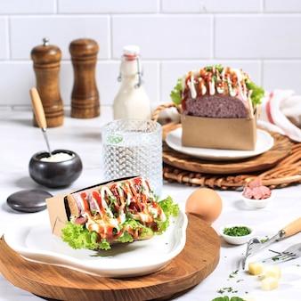 卵、レタス、マヨネーズ、ソース、チーズが入った2つの韓国サンドイッチ紫パン(エッグドロップ)。真水を添えて。